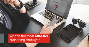 Image of a person holding a phone in his right hand and an opened laptop in front of him with a text on the image showing what is the most effective marketing strategy?