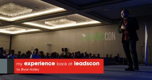 Image of a person standing on stage with many audiences and a text over the image showing my experience back at leadscon by Bryan Kofsky